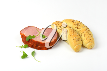 stack of sliced smoked pork meat with arugula leaves and bread rolls on white background