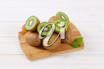 pile of whole and halved kiwi fruits on wooden cutting board