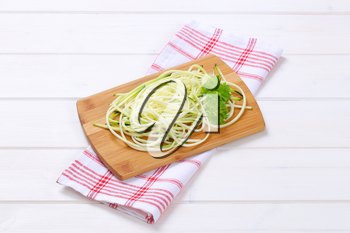 heap of raw zucchini noodles on wooden cutting board