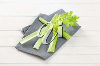 stems of green celery on grey place mat