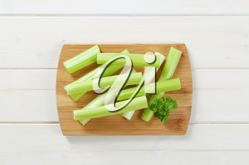 stems of green celery on wooden cutting board