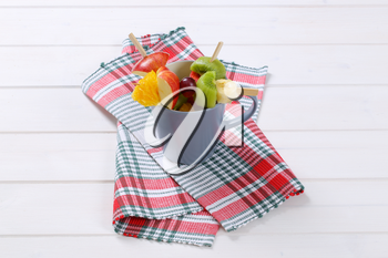 cup of fresh fruit skewers on checkered dishtowel