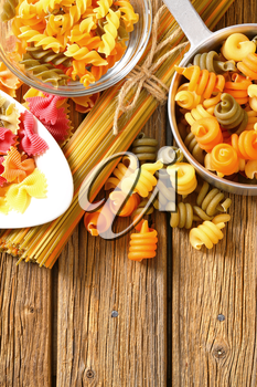 Various types of coloured pasta on a wooden background