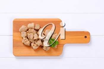 pile of soy meat cubes on wooden cutting board