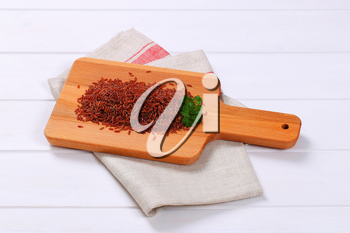 pile of red rice on wooden cutting board