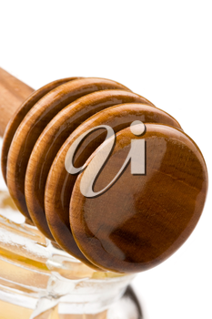 honey in glass jar and wooden stick isolated on white background