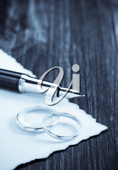 wedding ring and aged paper on wooden background