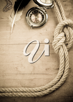 ship ropes and compass on wood background