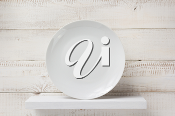 plate at shelf on white wooden plank background