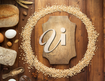 wheat grains and bakery ingredients on wooden background, top view
