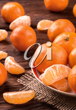 Plate with mandarins fruits and scattered slices on the table