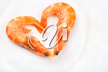 Boiled shrimp in a heart shape on a white plate closeup