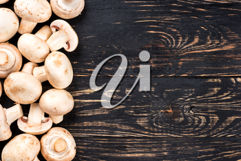 Scattered champignon mushrooms on a blank wooden background