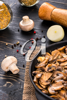 Cooking fried mushrooms champignon with ingredients on the table
