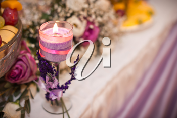 Candle on a table with a bouquet and ornaments.