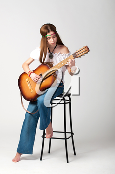 Studio photo of the girl with long hair with a guitar on a grey background.