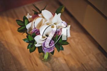 A beautiful bouquet of flowers stands in a vase on the floor.