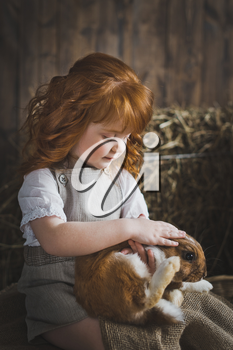 Child stroking a rabbit on her knees.