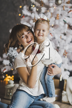 Happy mother holding her daughter in her arms on the background of Christmas decorations.