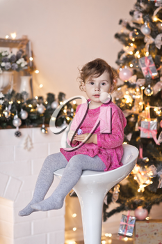 Portrait of a child on a background of Christmas lights garlands on the tree.