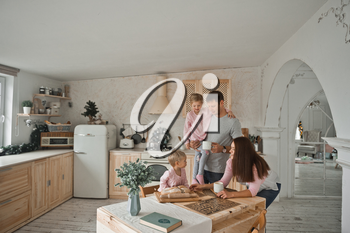 A young family with two daughters is preparing in the kitchen for the new year.