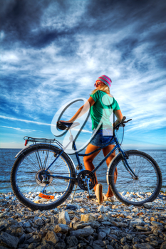 girl with a bicycle on the beach by the sea