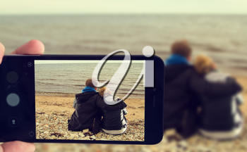 photographed on a smartphone sitting at the ocean couple
