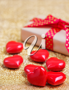 box for present and red hearts on a table
