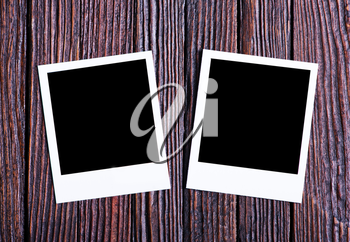 Blank instant photo on the wooden background