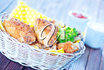 fried chicken wings in basket and on a table