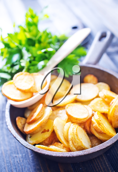 fried potato in pan and on a table