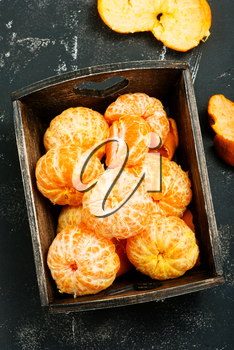 tangerines in wooden box and on a table