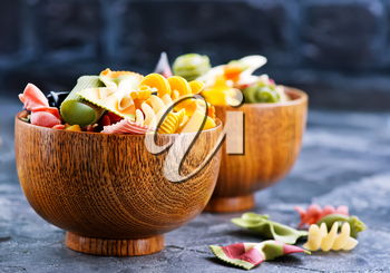 color raw pasta in bowl and on a table