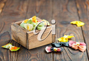 color raw pasta in wooden box and on a table