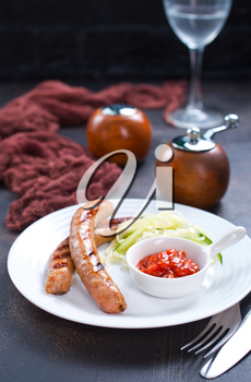 grilled sausages with sauce on white plate