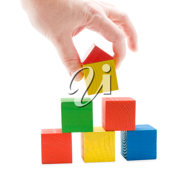 Hand establishes toy house on the wooden cubes pyramid. Isolated on white background.