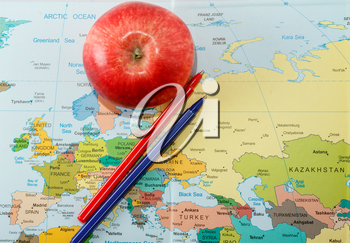 Red apple and pens on the map of Europe