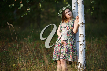 Girl with a wreath of wild flowers. Sunset light. Shallow depth of field. Focus on model.