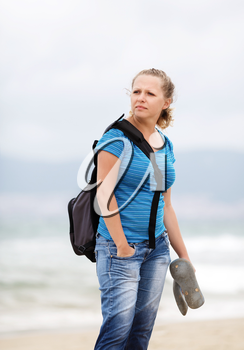 Pretty young serious blonde woman with a backpack outdoors. Girl with backpack. Selective focus on model. Vertical shot.