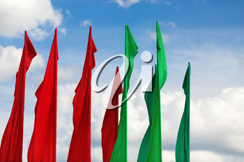 Several flagpoles with vertical green and red flag against a blue sky.