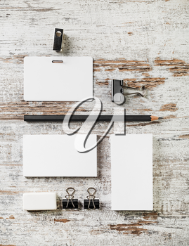 Photo of blank stationery set. Bank business cards, pencil, eraser, badge and sharpener on vintage wood table background. Template for design portfolios.Top view.