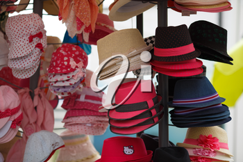 Nesebar, Bulgaria - September 02, 2014: Many variety colored hats for sale in the market. Selective focus.
