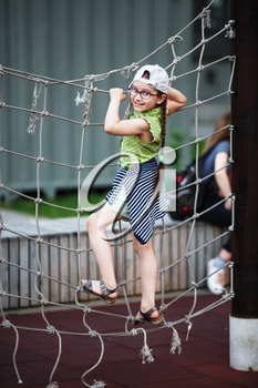 Happy girl on outdoor playground climbing frame. Child on rope climbing frame. Selective focus.