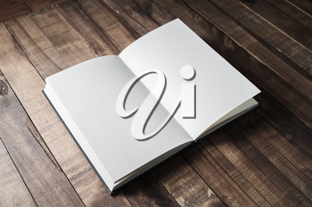 Blank open book, brochure or notebook on wooden table background. Responsive design mockup.