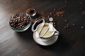Still life with coffee cup, roasted coffee beans and ground powder on wooden kitchen table background.