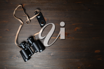 Old black military binocular on wood table background. Copy space for your text. Flat lay.
