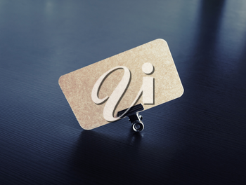 Blank vintage business card and metal binder clip on black wood table background. Copy space for text.
