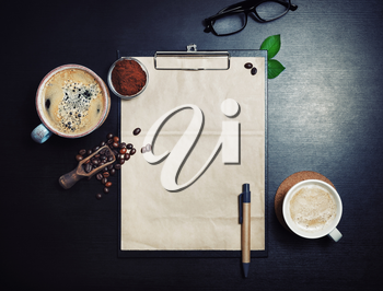 Clipboard with blank kraft letterhead, coffee cups, roasted coffee beans, pen and coffee ground on black table background. Space for text. Top view. Flat lay.