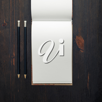 Blank open notebook or brochure and pencils on wood table background. Responsive design mockup. Top view. Flat lay.