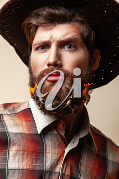 Young man in a cowboy hat and toy horses in a beard